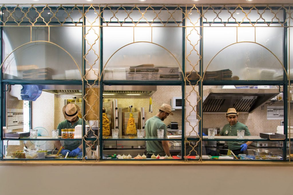 carne kosher vetrina di separazione sala-laboratorio con kebab sullo sfondo e operatori in divisa