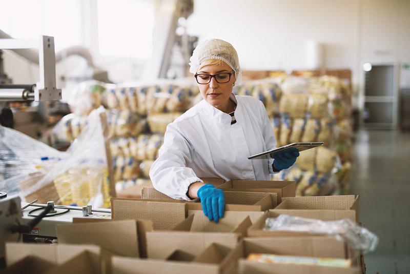 donna in divisa in magazzino che fa inventario
